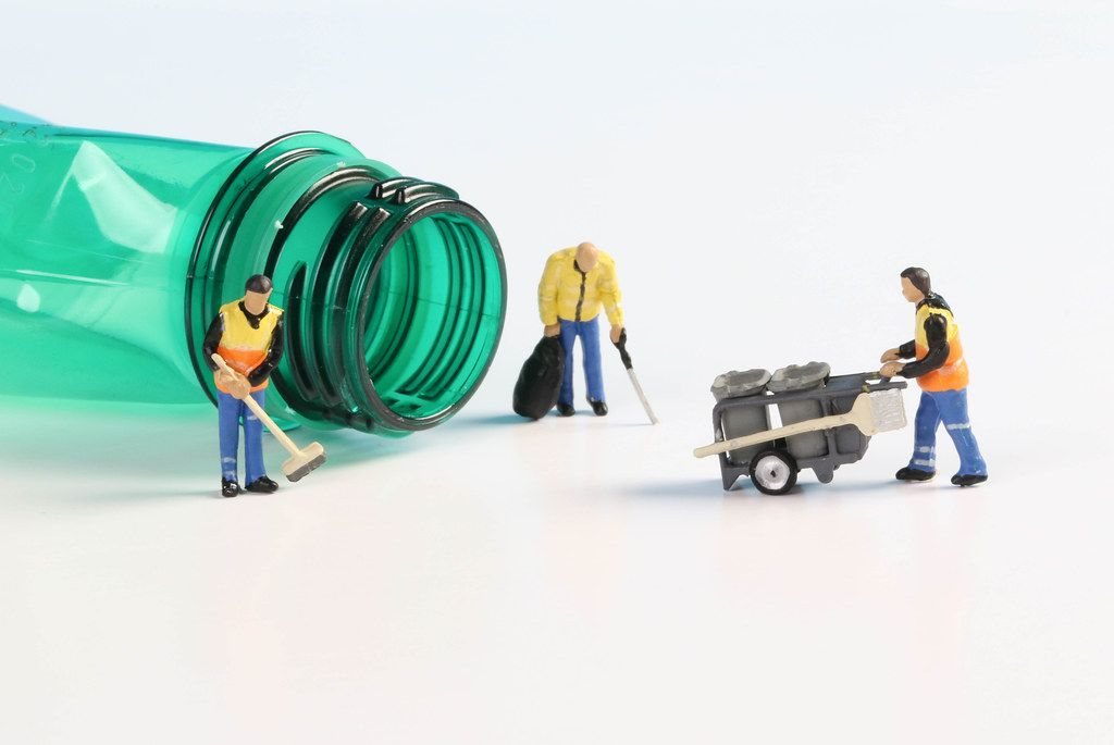 Miniature cleaning workers with empty plastic bottle