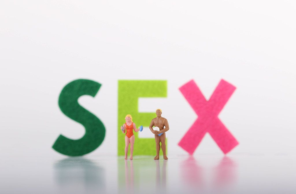 Miniature couple in swimwear stading in front of Sex text on white background