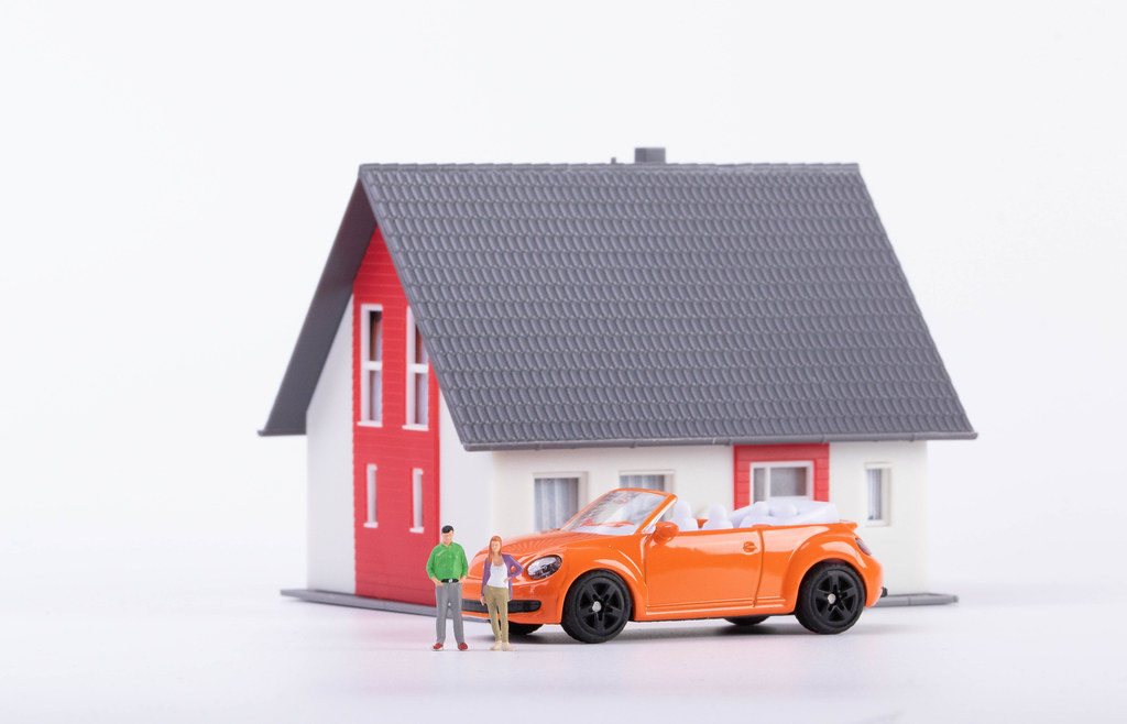 Miniature couple with orange car and a house on white background