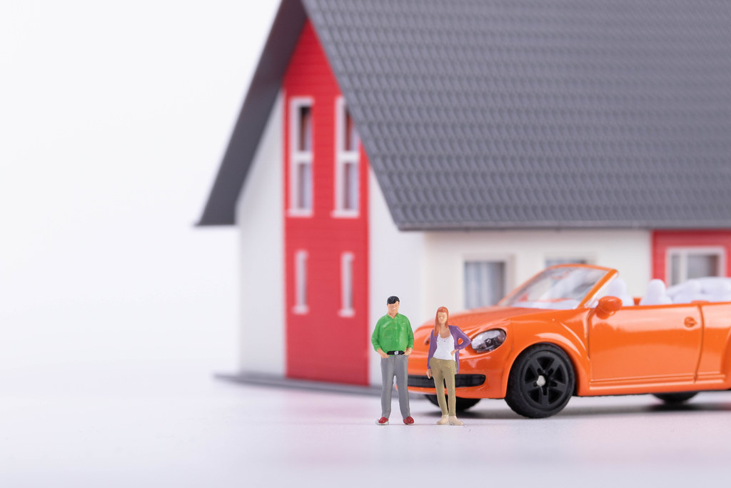 Miniature couple with orange car and a house