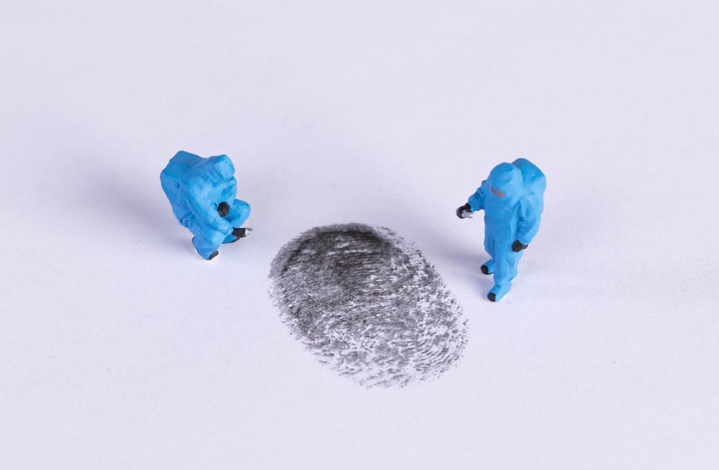 Miniature crime investigators with a finger print