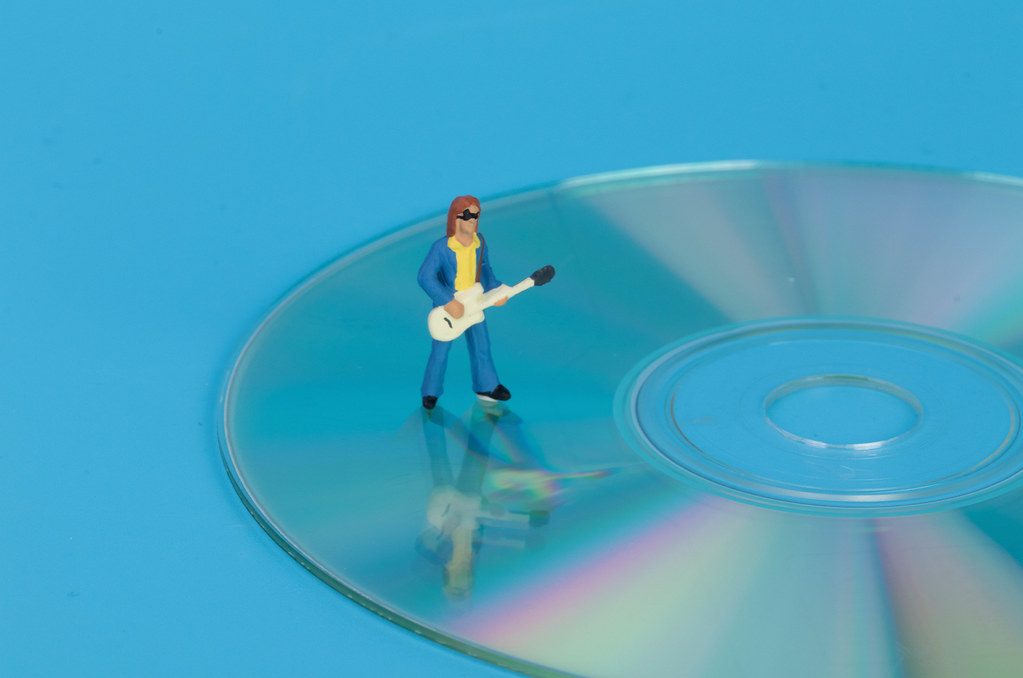 Miniature guitar player standing on CD