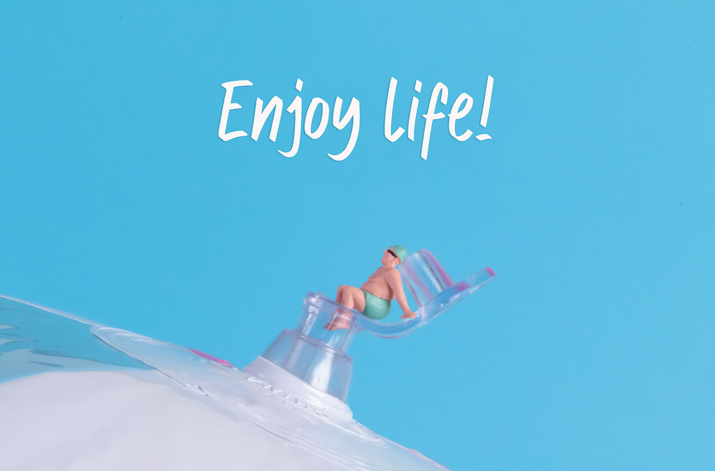Miniature man in swimsuit sitting on a beach ball with Enjoy Life text