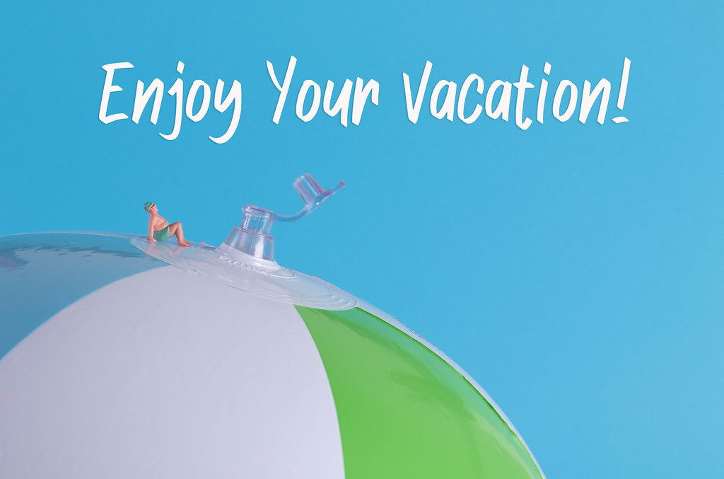 Miniature man in swimsuit sitting on a beach ball with Enjoy Your Vacation text