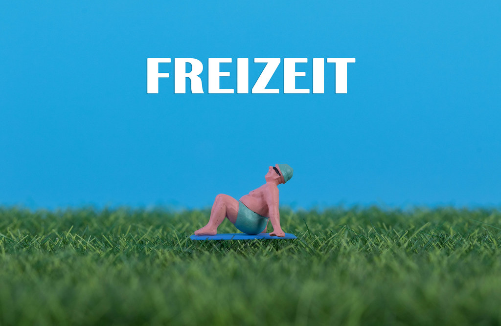 Miniature man relaxing on green grass with Freizeit text