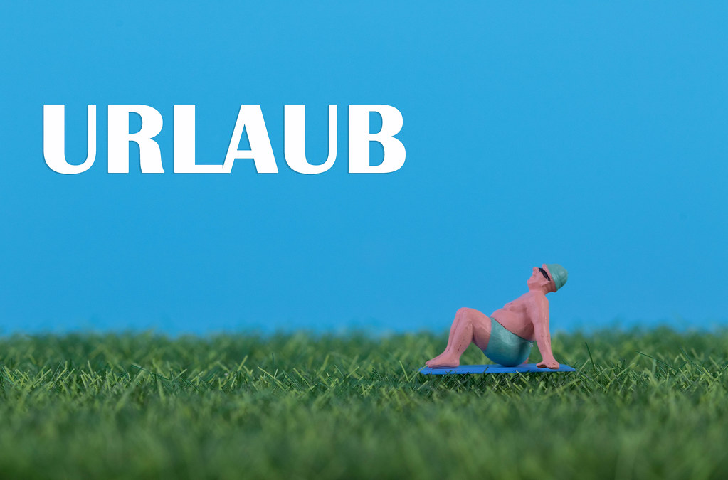 Miniature man relaxing on green grass with Urlaub text