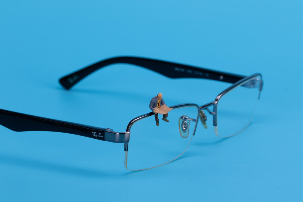 Miniature man sitting and reading on glasses