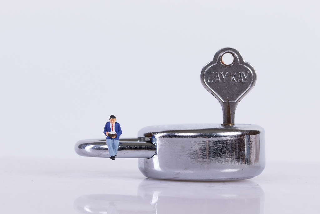 Miniature man sitting on a padlock