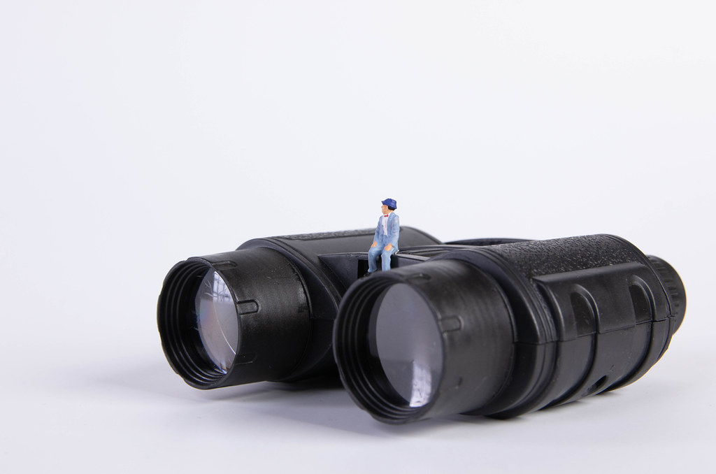 Miniature man sitting on binoculars