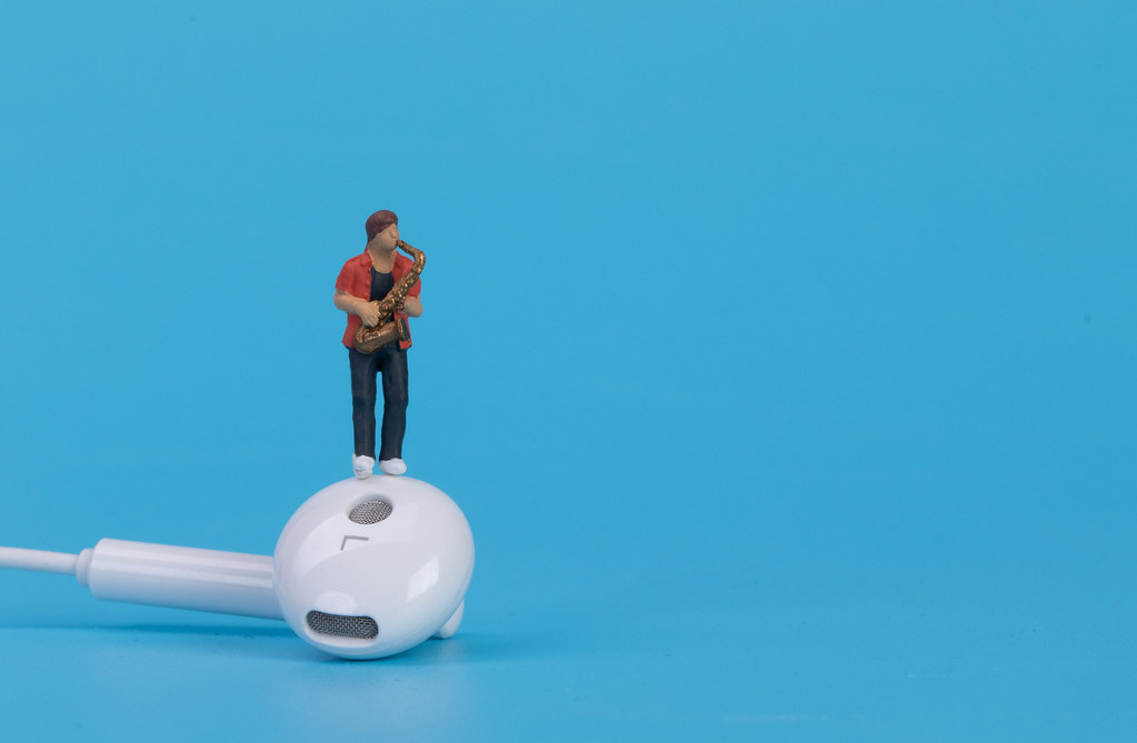 Miniature musician with earbud on blue background