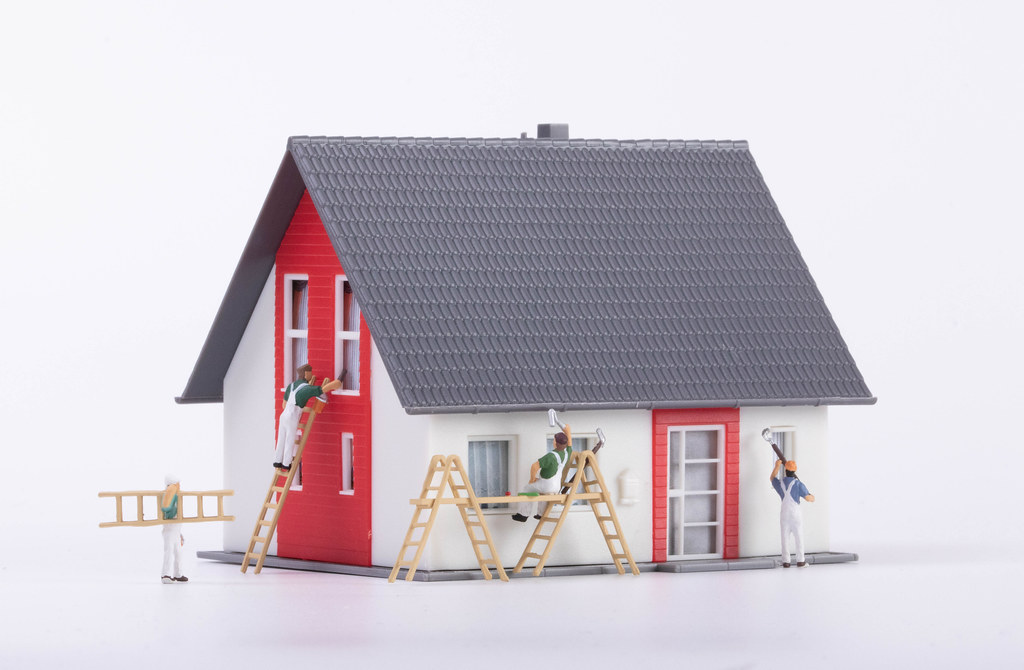 Miniature painters painting a house