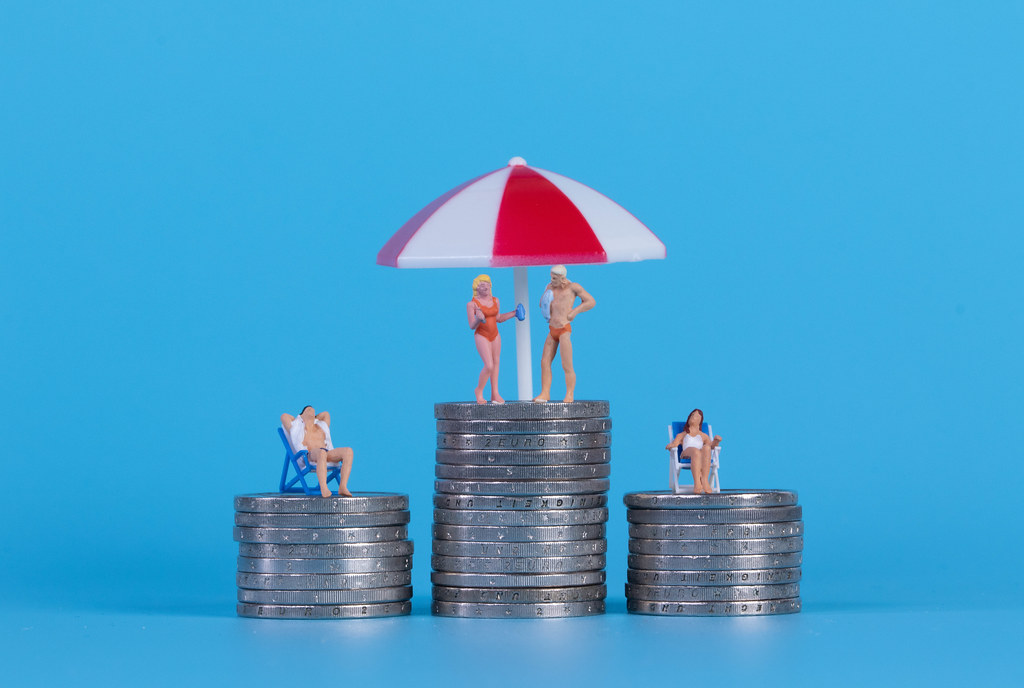 Miniature people in swimsuit on a top of coinstacks with blue background