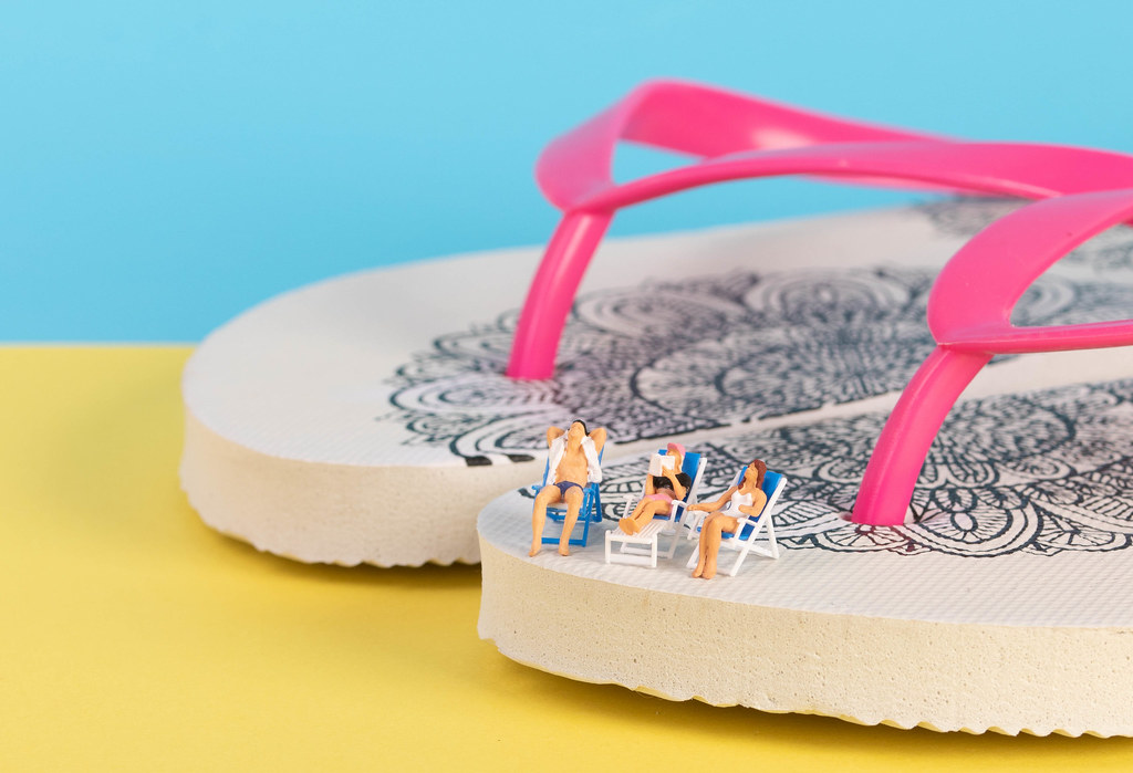 Miniature people sitting in deck chairs on top of the flip flops