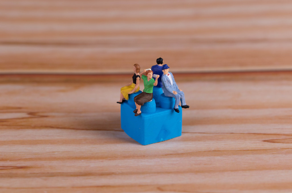 Miniature people sitting on plastic building block