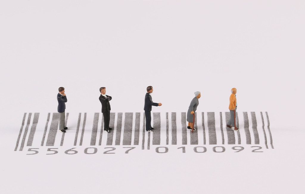 Miniature people standing on bar code