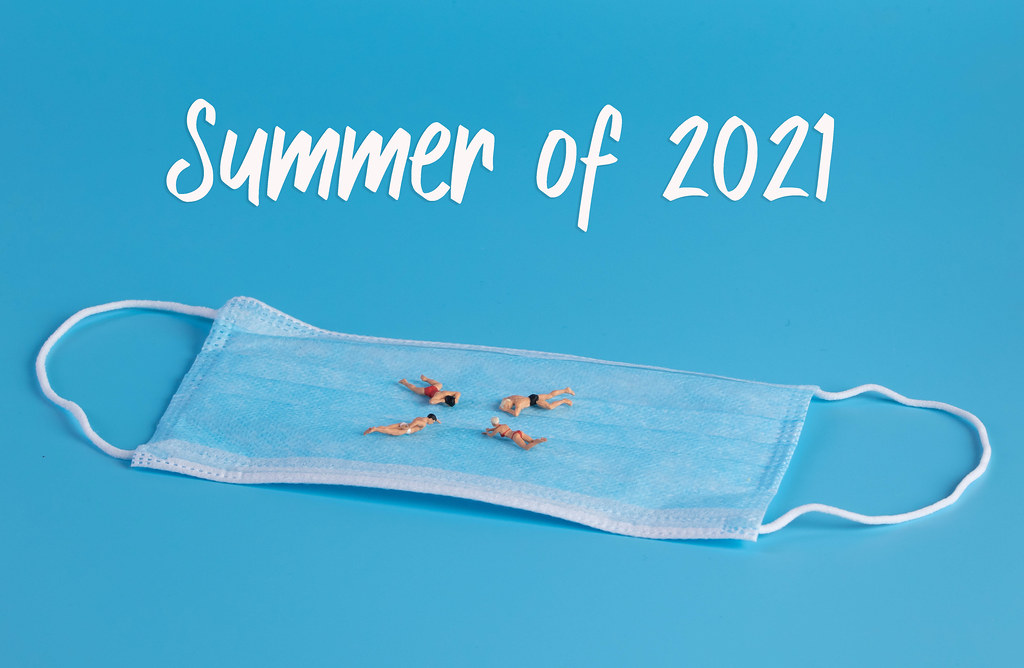 Miniature people swimming on medical face mask and Summer of 2021 text