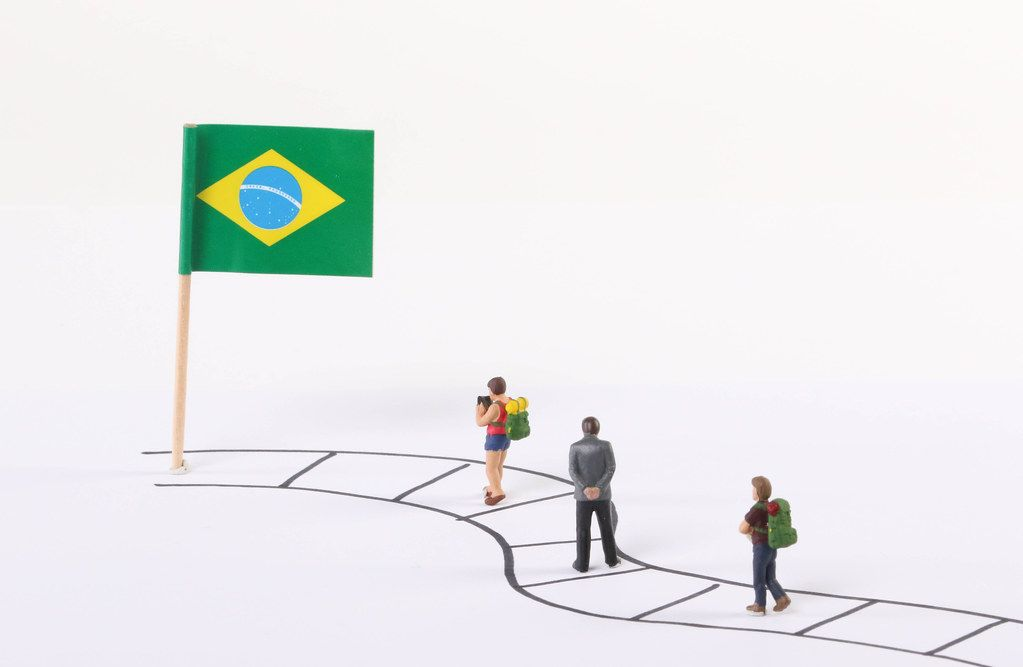 Miniature people walking on a path to the flag of Brasil