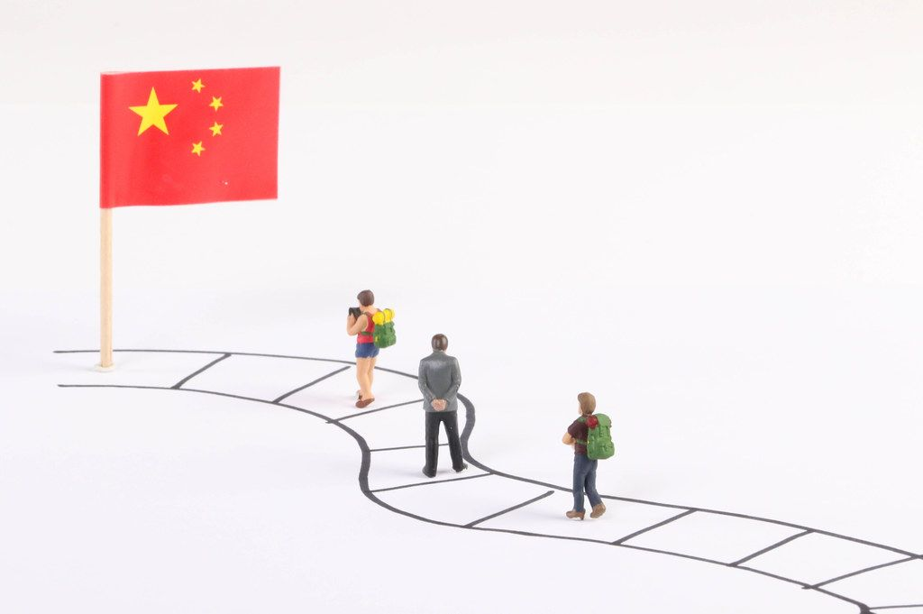 Miniature people walking on a path to the flag of China