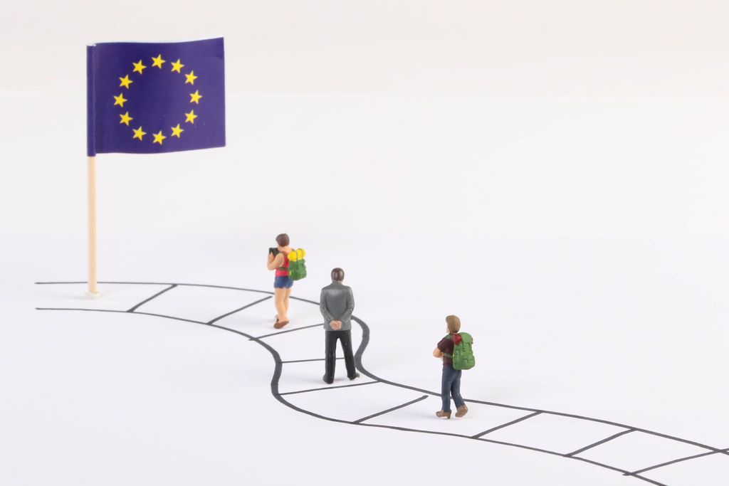 Miniature people walking on a path to the flag of European Union