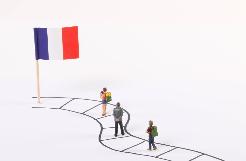 Miniature people walking on a path to the flag of France