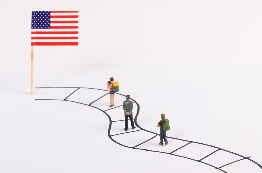 Miniature people walking on a path to the flag of USA