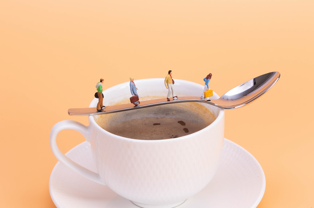 Miniature people walking on the spoon over the hot cup of coffee