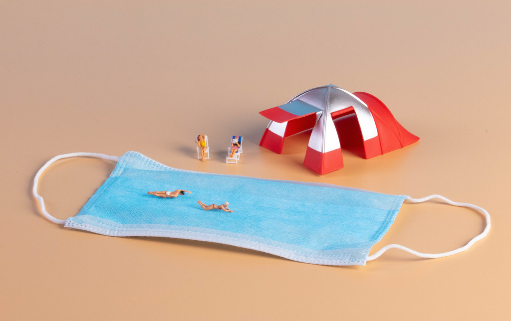 Miniature people with camping tent and medical face mask