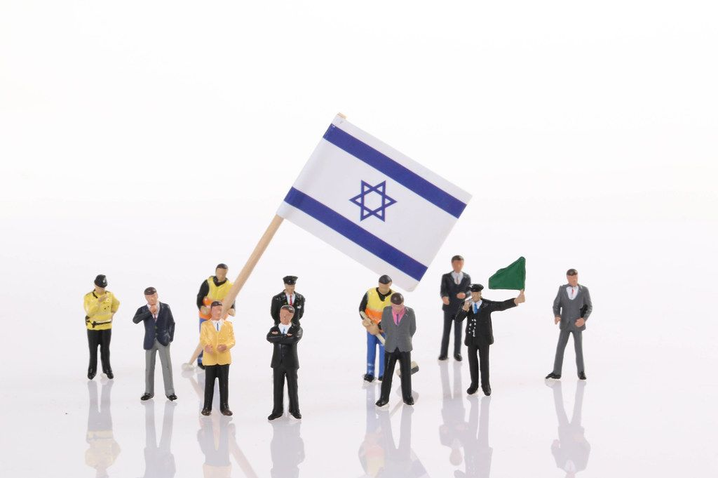 Miniature people with flag of Israel