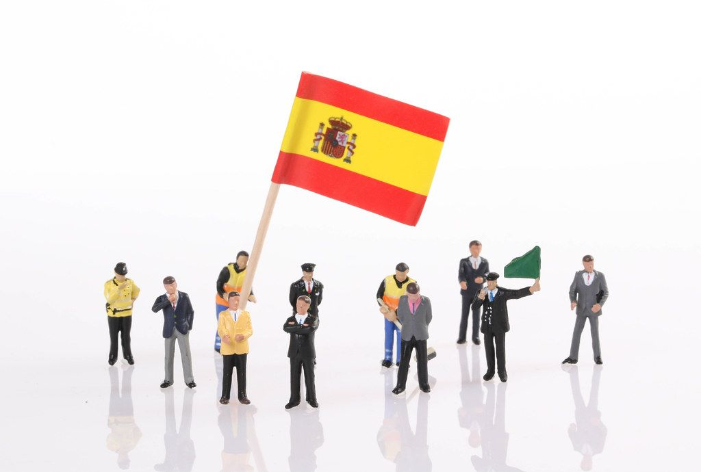 Miniature people with flag of Spain