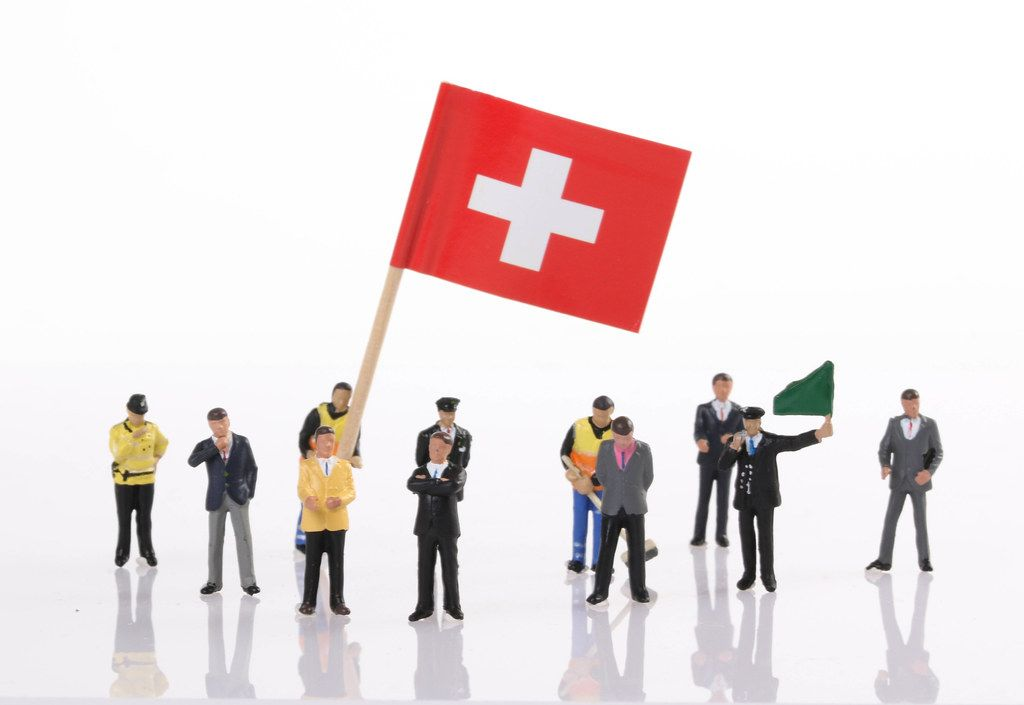 Miniature people with flag of Switzerland
