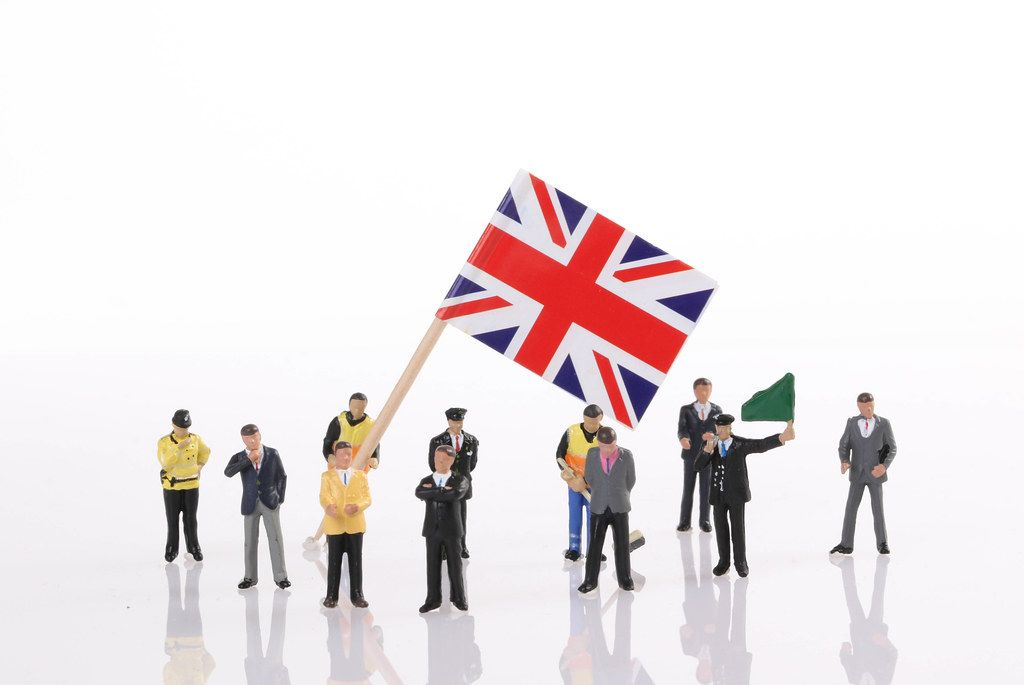 Miniature people with flag of United Kingdom on white background