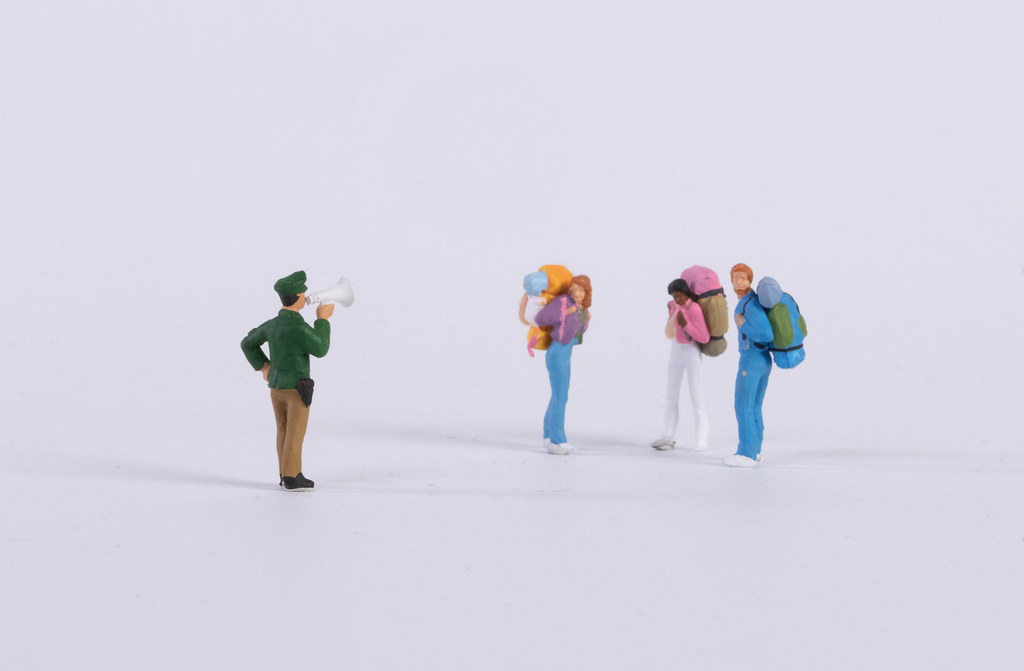 Miniature policeman with group of backpackers on white
