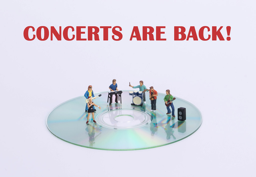 Miniature rock band standing on CD and Concerts are back text