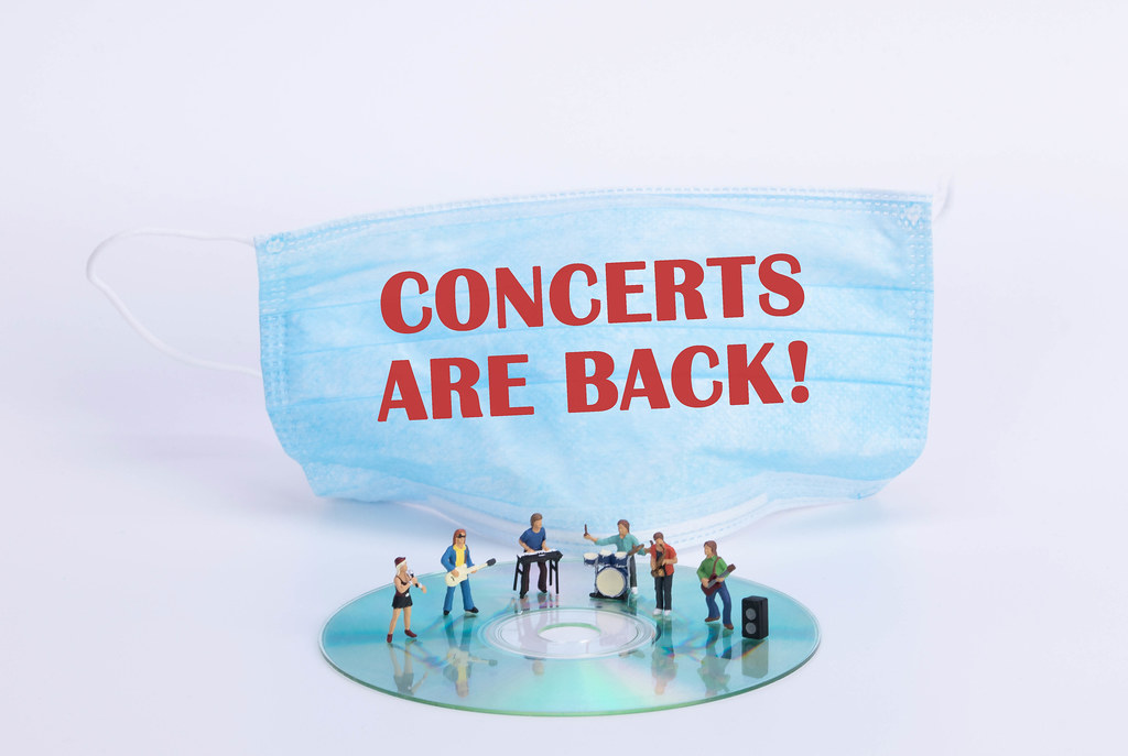 Miniature rock band standing on CD and medical face mask with Concerts are back text