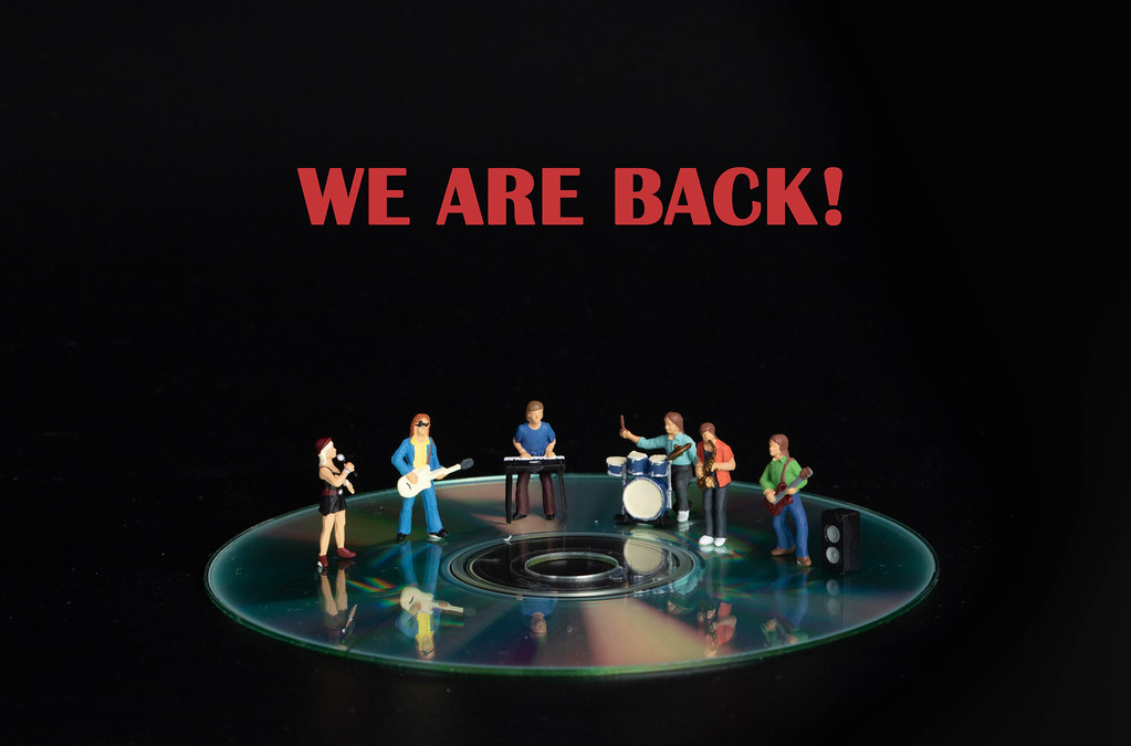 Miniature rock band standing on CD and We are back text