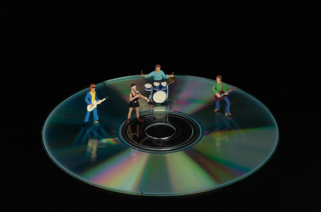 Miniature rock band standing on CD on black background