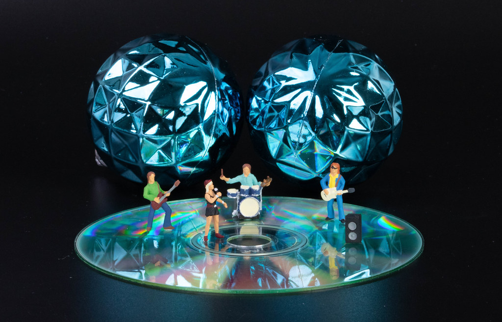 Miniature rock with blue Christmas balls and CD on black background