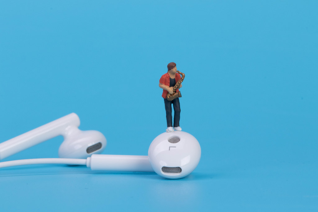 Miniature saxofonist with earbuds on blue background