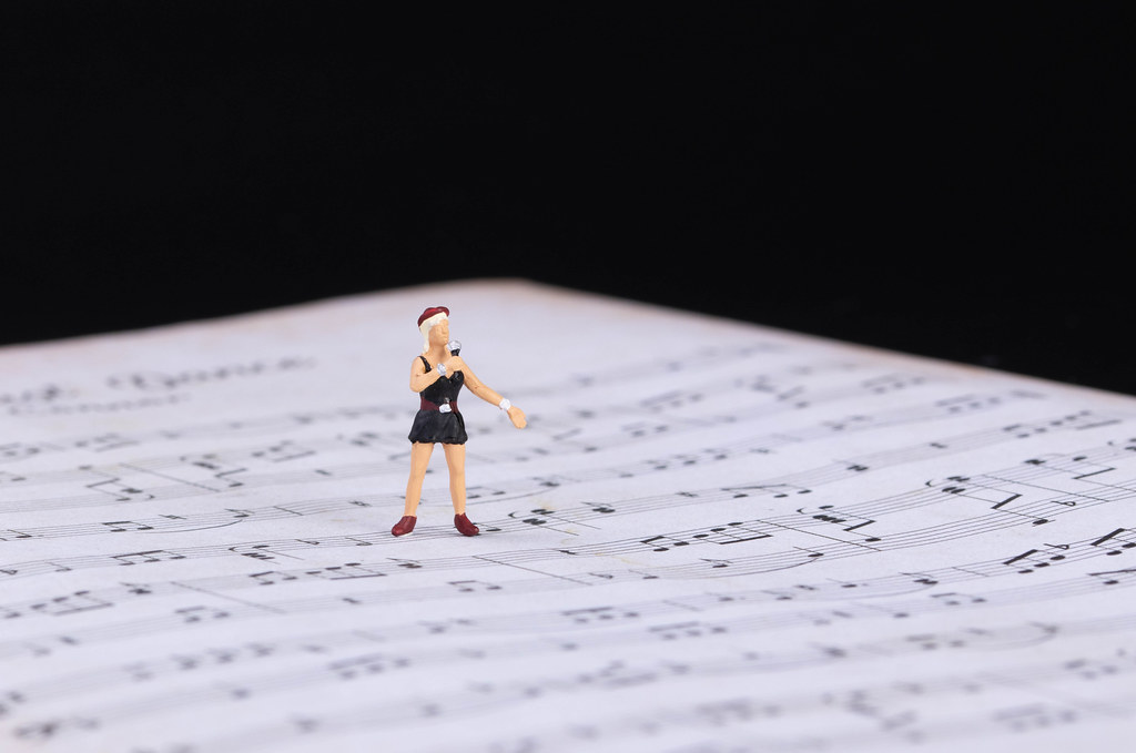 Miniature singer standing on music notes