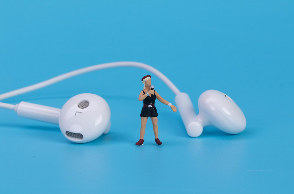 Miniature singer with earbuds on blue background