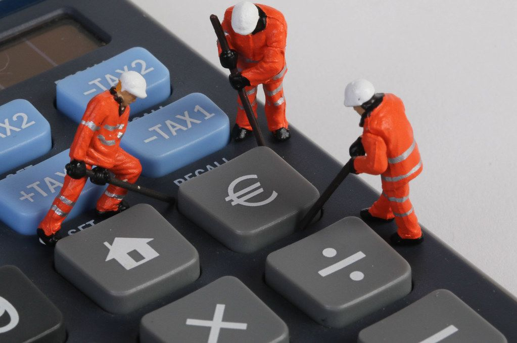 Miniature technician repairing Euro button on calculator