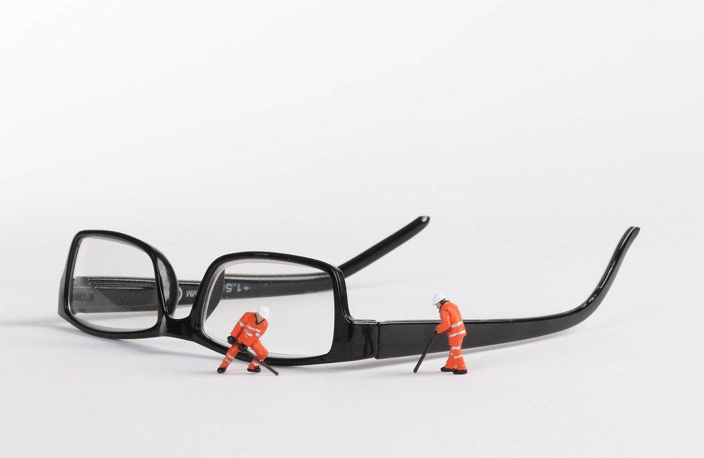 Miniature technician repairing reading glasses