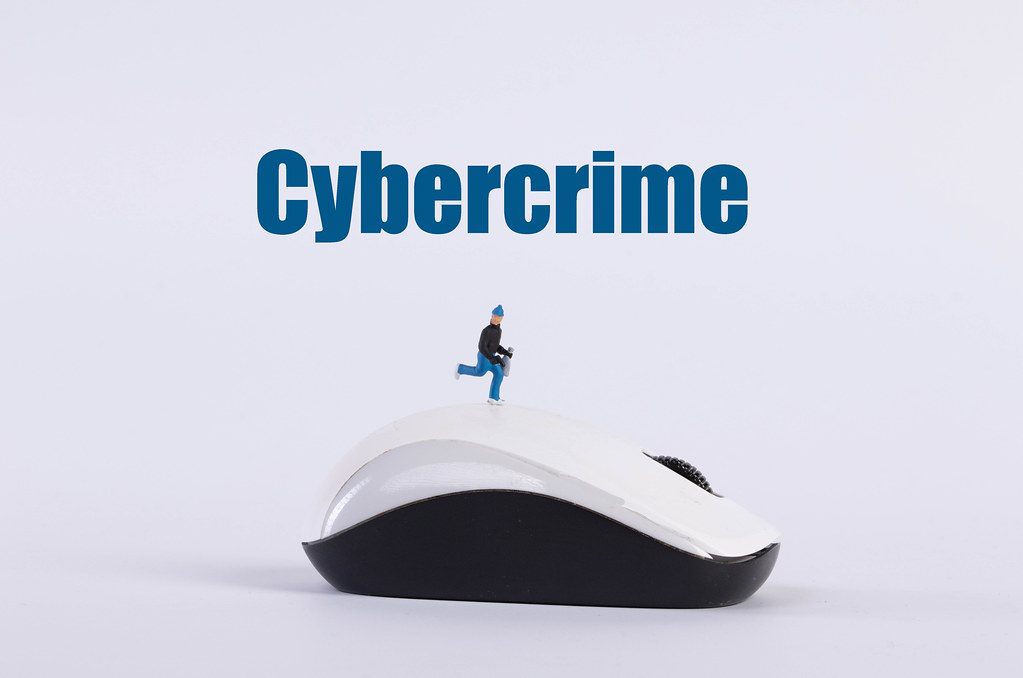 Miniature thief on a computer mouse with Cybercrime text