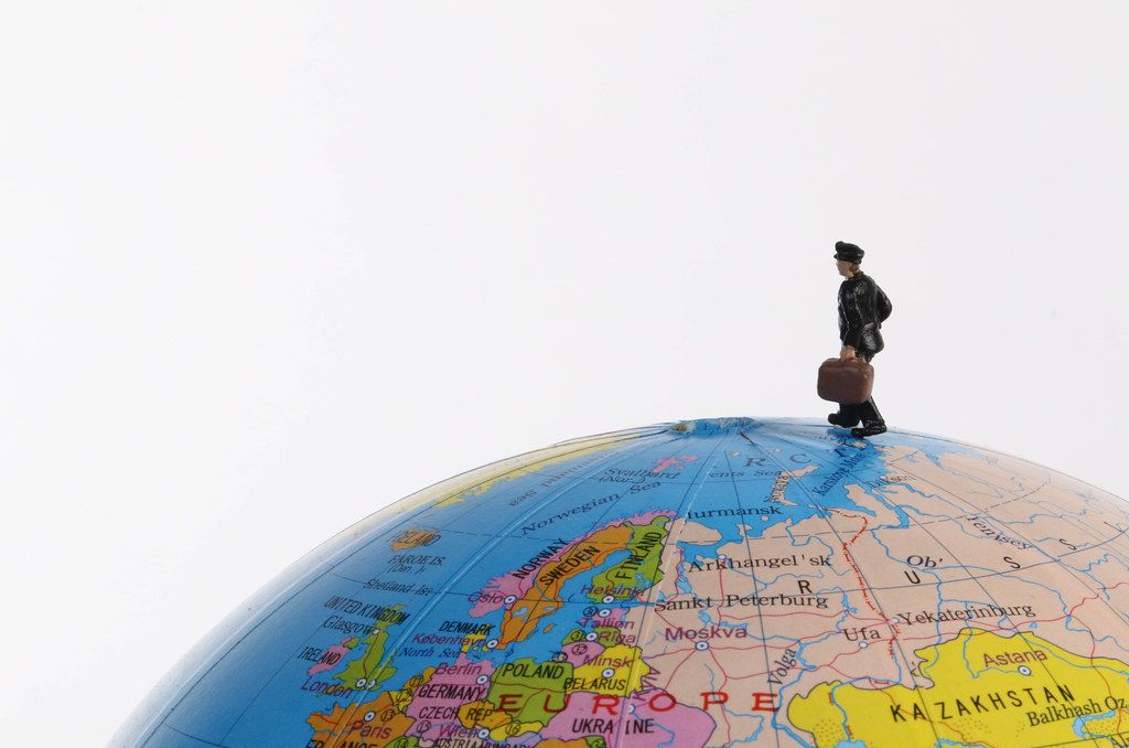 Miniature traveler man on the globe