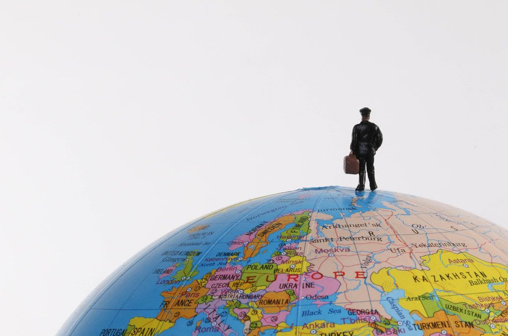 Miniature traveler man on the terrestrial globe