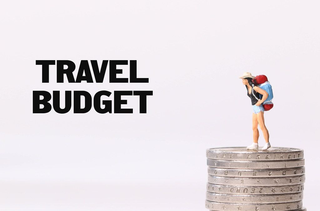 Miniature traveler standing on stack of coins and Travel Budget text
