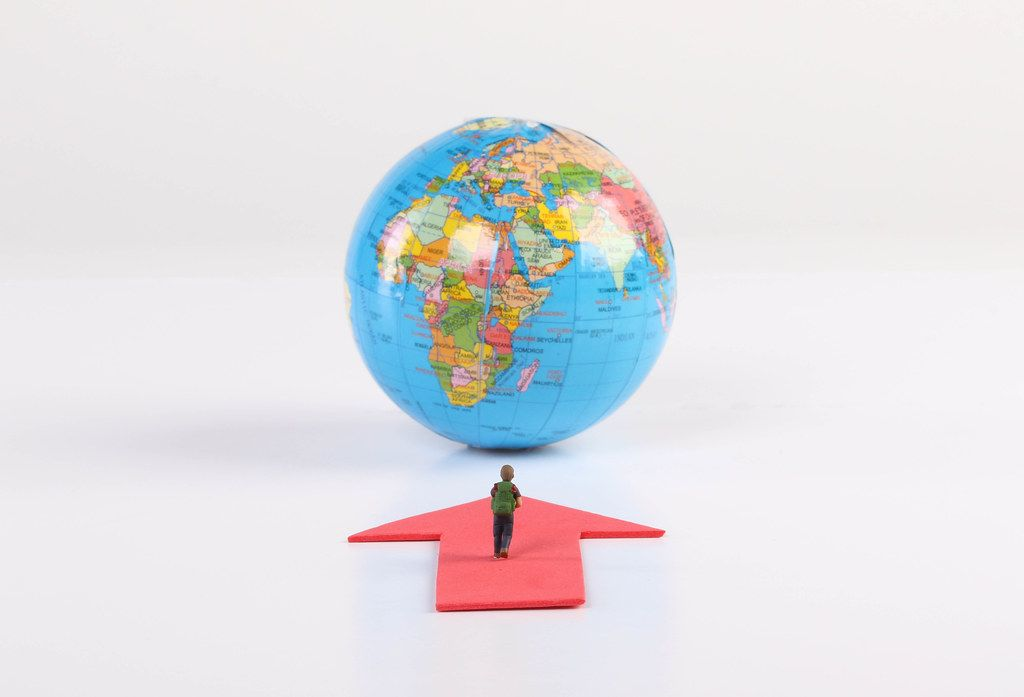Miniature traveler with red arrow and globe on white background