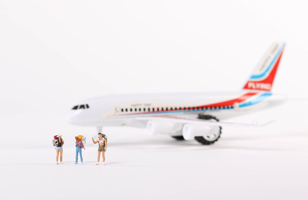 Miniature travelers and airplane on white background