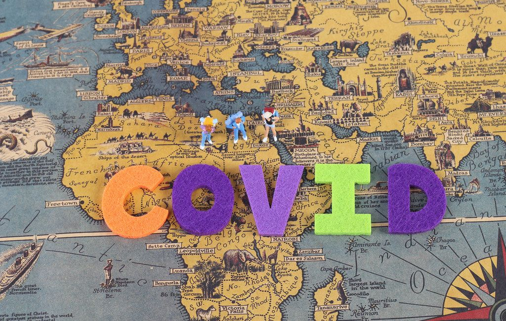Miniature travelers on the map with Covid text
