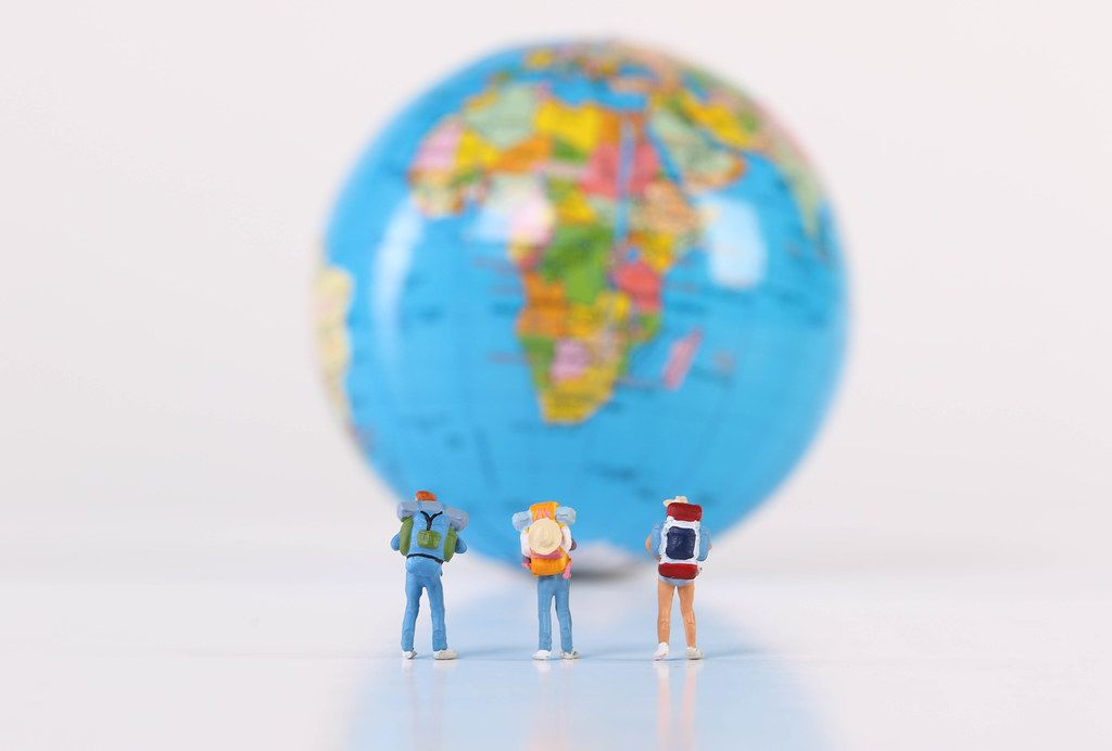 Miniature travelers stading in front of globe